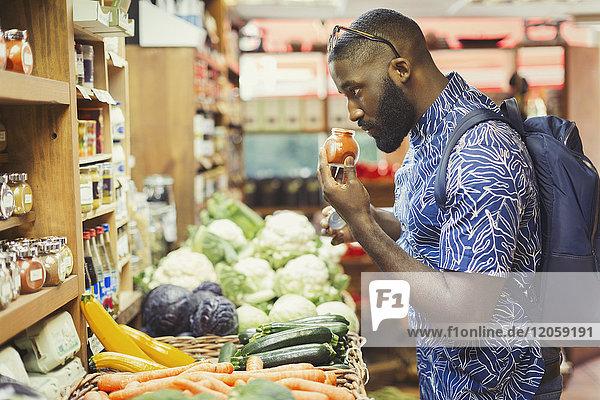 Mann einkaufen  Gewürze riechen im Lebensmittelgeschäft