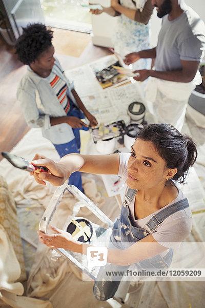 Junge Frau malt Wohnzimmer mit Freunden