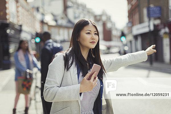 Junge Geschäftsfrau mit Handy-Hageltaxi auf sonniger Stadtstraße