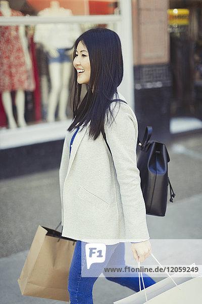 Lächelnde junge Frau geht mit Einkaufstaschen an der Schaufensterfront entlang.