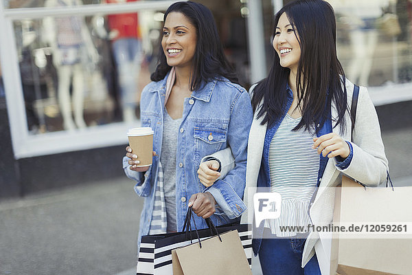 Smiling women friends walking arm in arm along storefront with coffee and shopping bags