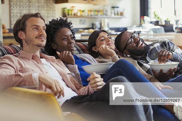 Paare sehen fern und essen Popcorn auf dem Wohnzimmersofa.