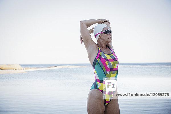 Schwimmerin im offenen Wasser  die den Arm am Meer streckt.
