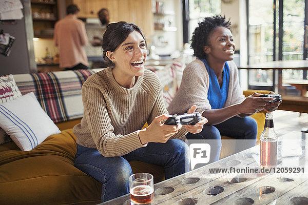 Lachende Freundinnen beim Videospiel auf dem Wohnzimmersofa
