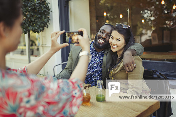 Woman photographing affectionate couple friends with camera phone at sidewalk cafe