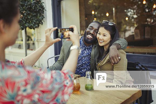 Frau fotografiert liebevolle Pärchenfreunde mit Fotohandy im Bürgersteigcafé