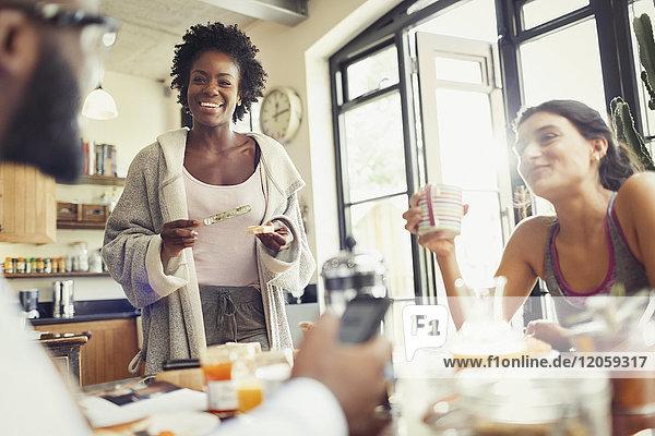 Junge Mitbewohner beim Frühstück am Küchentisch