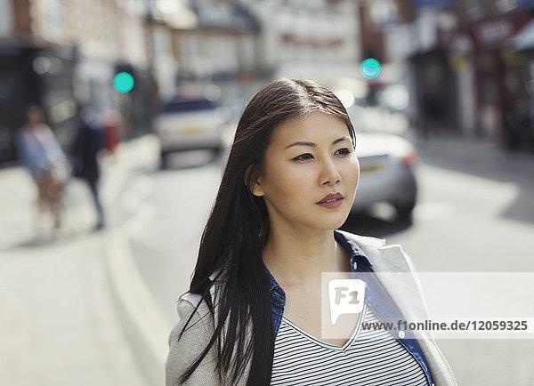 Seriöse  nachdenkliche junge Frau  die auf einer städtischen Straße geht.