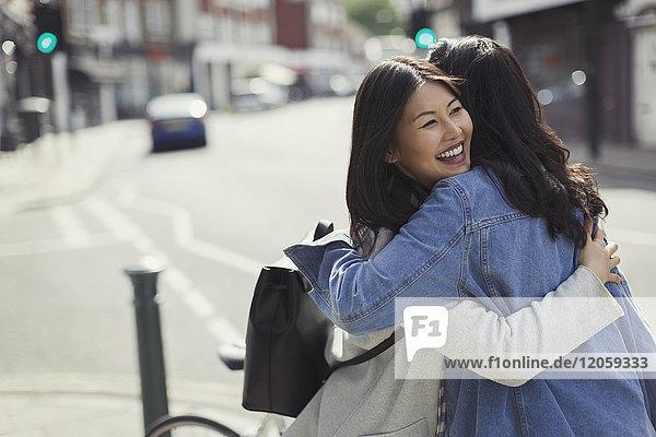 Smiling affectionate female friends hugging on sunny urban street