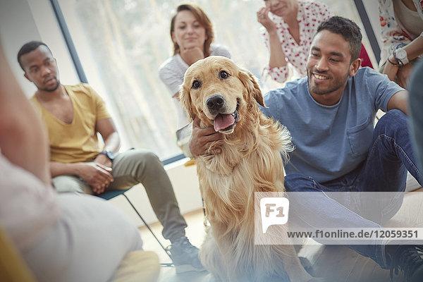 Mann Streichelhund in der Gruppentherapie