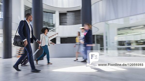 Geschäftsleute beim Gehen  Kofferziehen in der modernen Bürolobby
