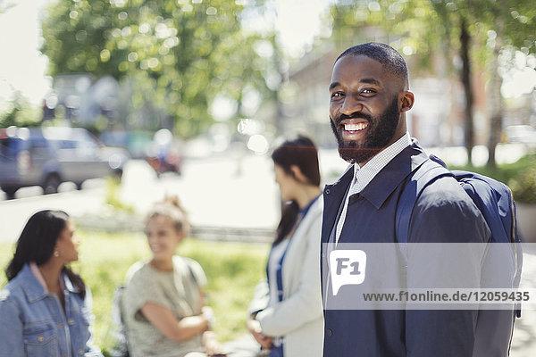 Portrait lächelnder Geschäftsmann mit Rucksack im Stadtpark