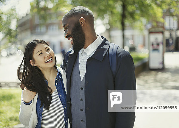 Affectionate couple laughing in sunny urban park