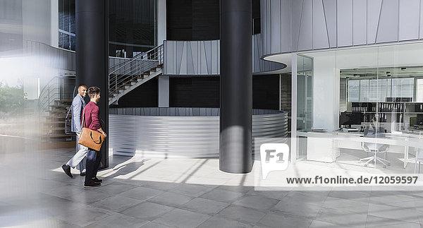 Geschäftsleute  die in der modernen Bürolobby spazieren gehen