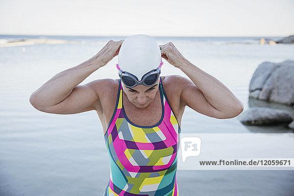Schwimmerin im offenen Wasser  die eine Schwimmbrille am Meer einstellt
