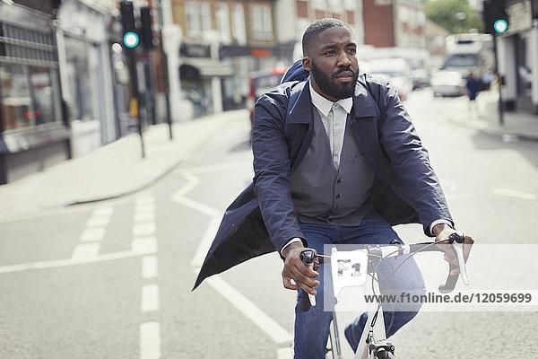 Junger Geschäftsmann  der mit dem Fahrrad auf einer sonnigen Stadtstraße pendelt.