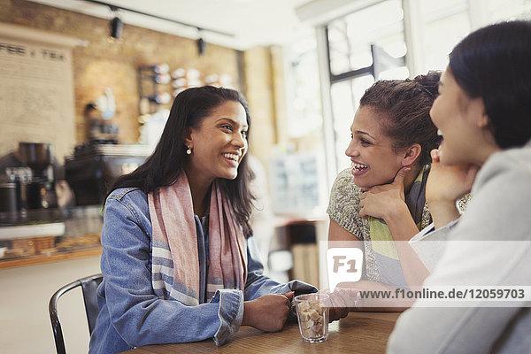 Lächelnde Freundinnen am Kaffeetisch