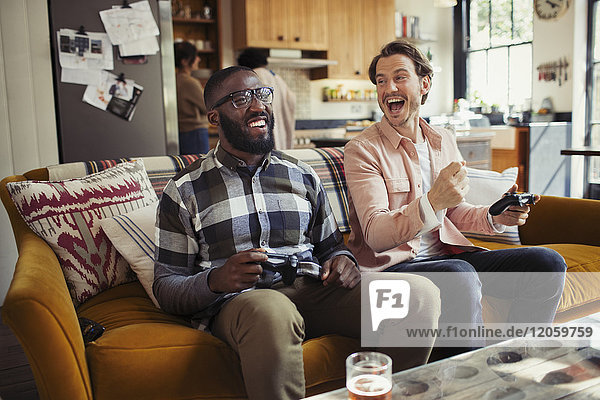 Laughing men friends playing video game on living room sofa