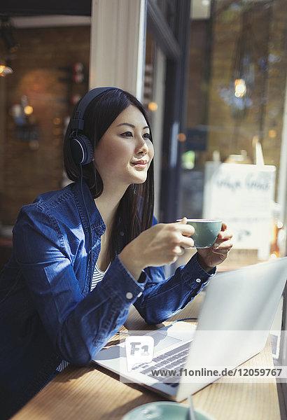Nachdenkliche junge Frau hört Musik mit Kopfhörern und trinkt Kaffee am Laptop im Caféfenster.