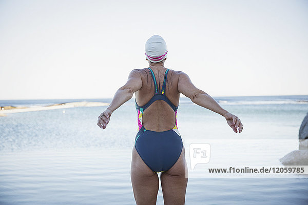 Weibliche Freiwasserschwimmerin  die sich am Meer ausdehnt.