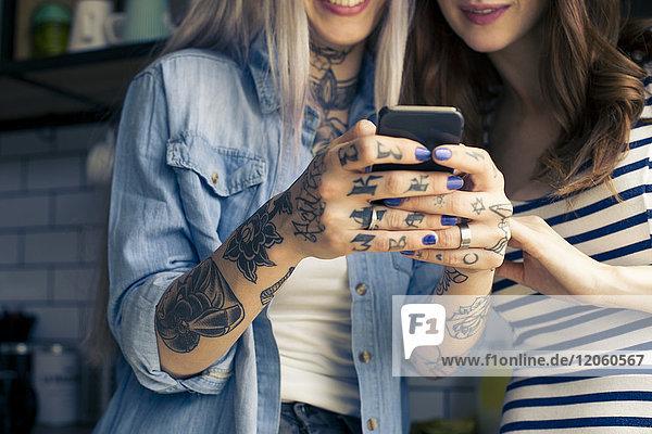 Junge Frauen  die zusammen auf das Smartphone schauen  abgeschnitten