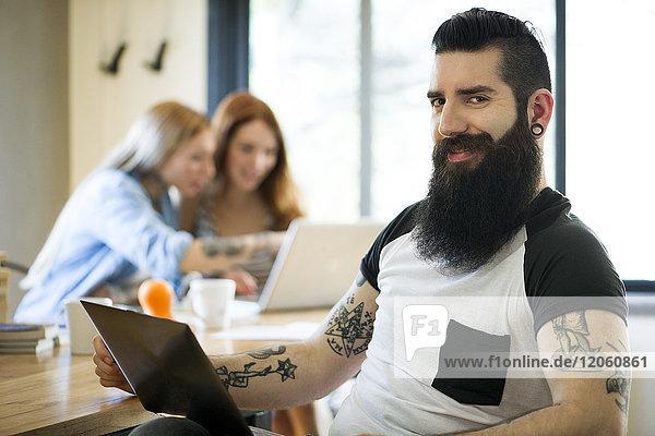 Mann mit Laptop  lächelnd  Portrait