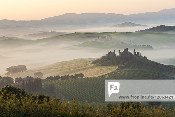 Sunrise across a misty Italian landscape of rolling hills and cypress trees  farmhouse in the distance.