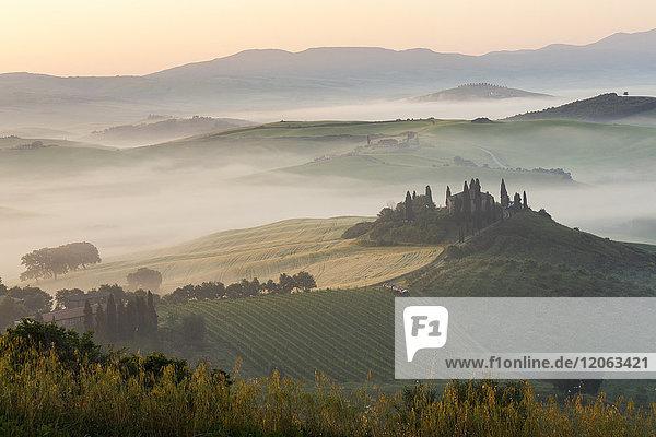 Sonnenaufgang über einer nebligen italienischen Landschaft mit sanften Hügeln und Zypressen  in der Ferne ein Bauernhaus.