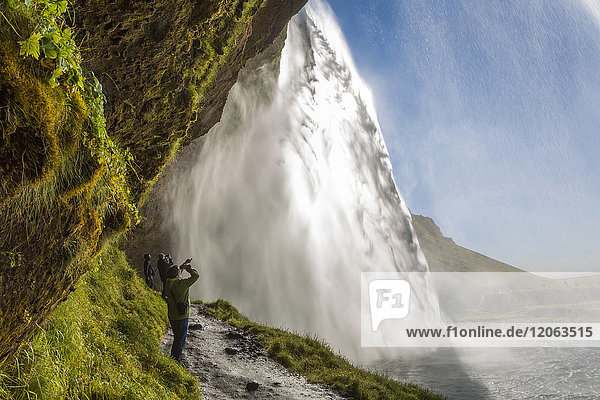 People standing on a narrow path underneath a waterfall cascade over a sheer cliff.