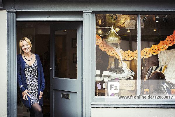 Eine Frau steht in der Türöffnung ihres aufspringenden Inneneinrichtungsgeschäfts mit einer Schaufensterauslage von Gegenständen.