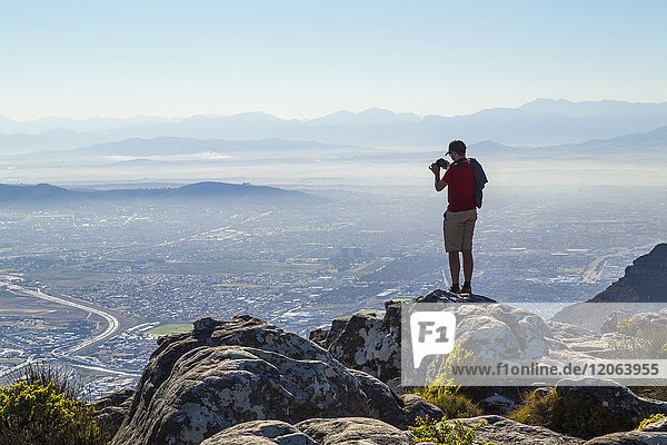 Man standing on rock on edge of mountain  photographing cityscape and mountain range in the distance.