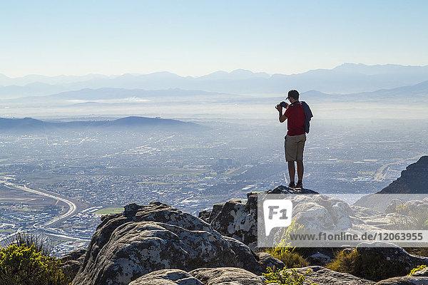 Mann steht auf einem Felsen am Rande eines Berges und fotografiert Stadtlandschaft und Gebirge in der Ferne.
