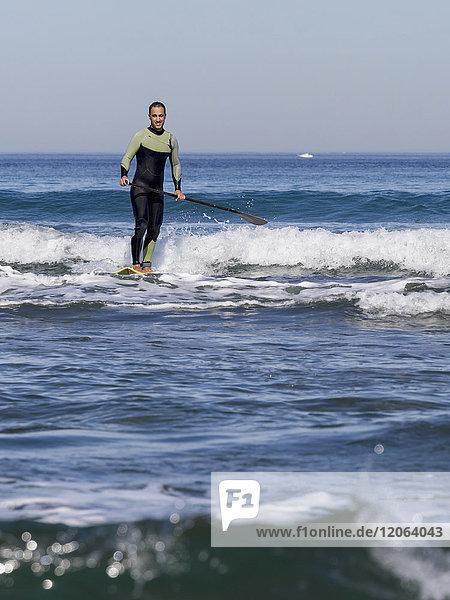 Man surfer craving top of wave at sopelana beach