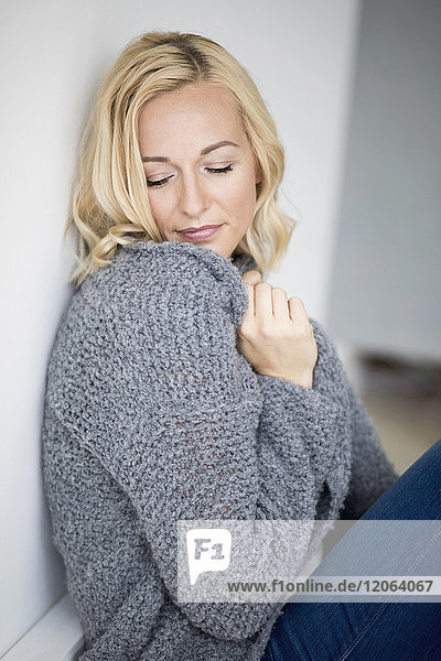 Beautiful woman leaning against wall with eyes closed