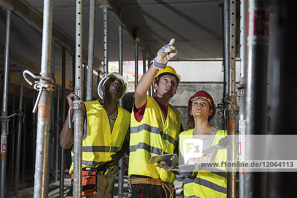 Construction workers with digital tablet and architectural plan at building site