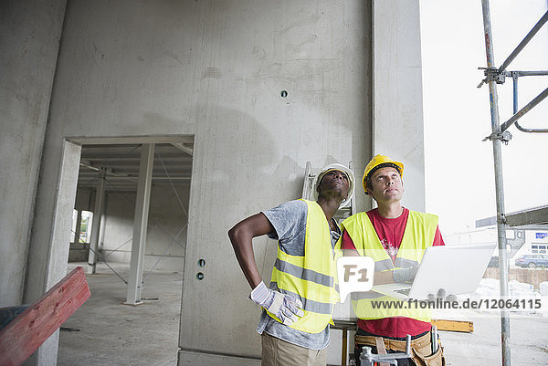 Construction workers with laptop at building site
