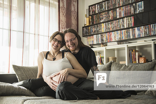 Portrait of pregnant couple relaxing on couch
