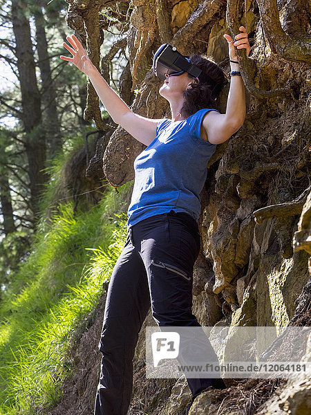 Woman wearing virtual reality headset in forest