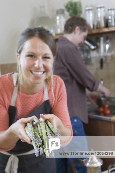 Couple preparing food  woman holding asparagus
