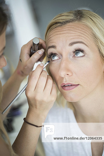 Woman having make-up applied by stylist