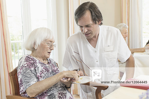 Caregiver giving medicine to senior woman at rest home