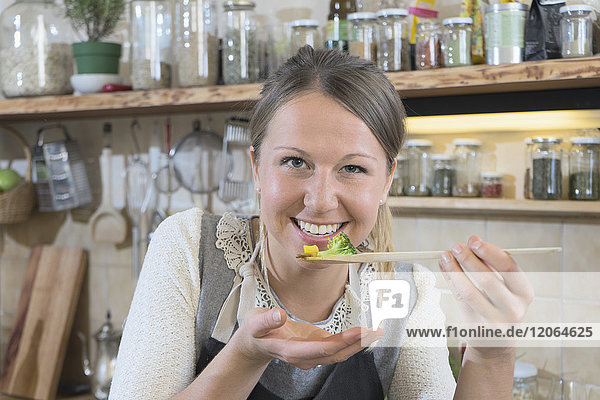 Woman tasting stir fried vegetables