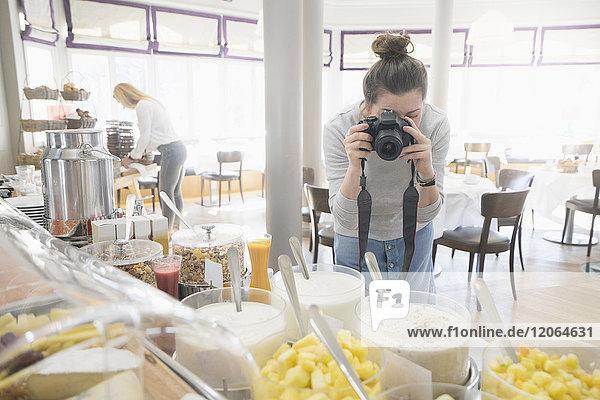 Woman taking photos of breakfast buffet