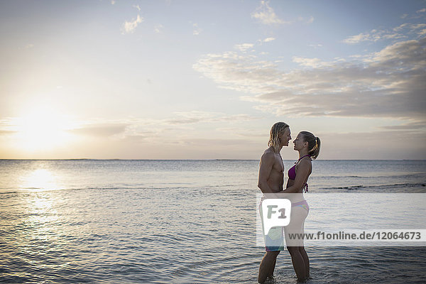 Young couple standing face to face at beach