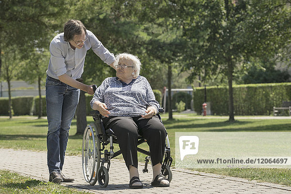 Son walking with disabled mother on wheelchair