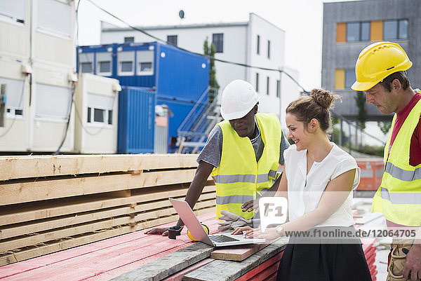 Architect using laptop with construction workers at building site