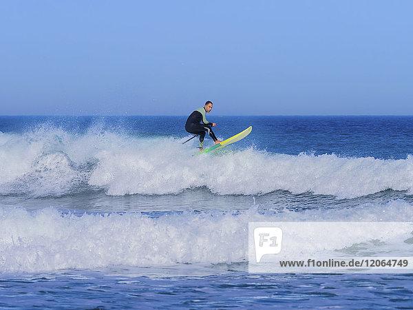 Man surfer riding crashing top of wave at sopelana beach