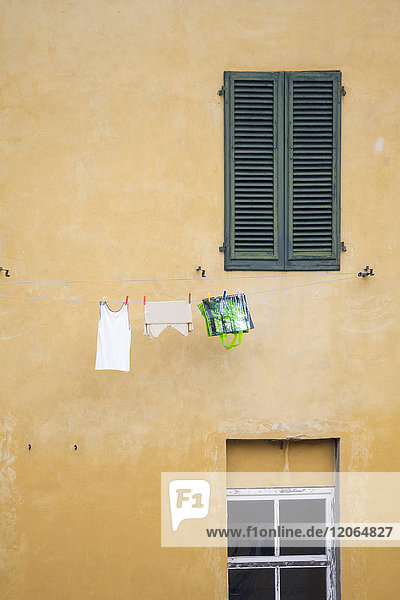 Laundry hanging on clothesline against house wall