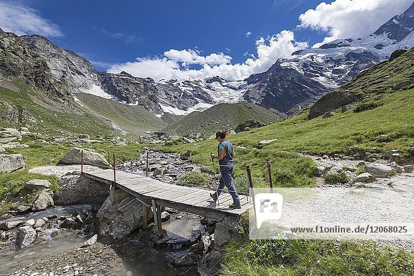A trekker crosses a small wooden bridge near the Zamboni Zappa refuge at the foot of the East face of Monte Rosa Massif (Macugnaga  Anzasca Valley  Verbano Cusio Ossola province  Piedmont  Italy  Europe).