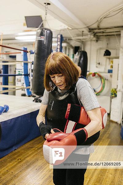 Seniorenfrau beim Anziehen von Boxhandschuhen